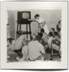 a group of children huddled around an antique television as a nurse adjusts the station